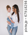Portrait of Little girl with mom in studio. White background 67918298
