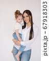 Portrait of Little girl with mom in studio. White background 67918303