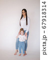 Little girl with mom in studio. White background 67918314