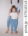 Little girl with mom in studio. White background 67918318