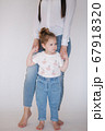 Little girl with mom in studio. White background 67918320