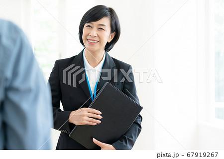 客に施設を案内するミドル女性 67919267