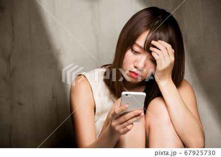 スマートフォン・憂うつな女性 67925730