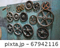 Gears on wooden panel 67942116
