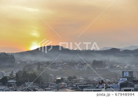 ほとんど日が沈みかけた美しい夕焼けを背景に、夕もやのかかった富士宮市 67948994