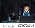 Attractive blonde working on laptop in dark office. Mixed media 67972814