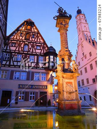 ロマンチック街道の名所である中世ドイツの佇まいを残すローテンブルクのライトアップされた街並みと噴水 67983214