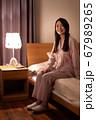 ベッドに座る女性 67989265