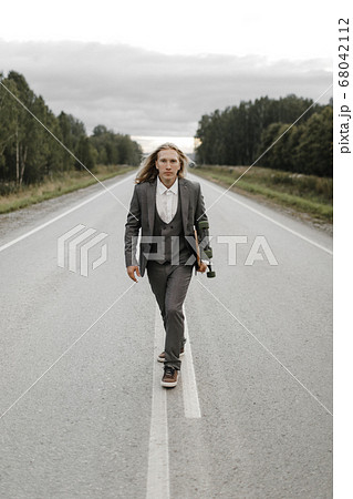 Handsome man in office suit with longboard walking down road in city outskirts. 68042112