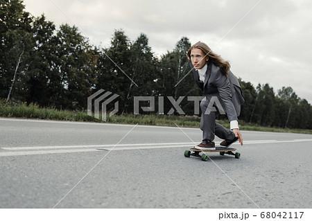 Man in office suit is riding skateboard longboard down road outside the city. 68042117