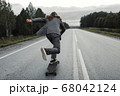 Man in office suit is riding skateboard longboard down road outside the city. 68042124