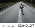 Man in office suit is riding skateboard longboard down road outside the city. 68042127