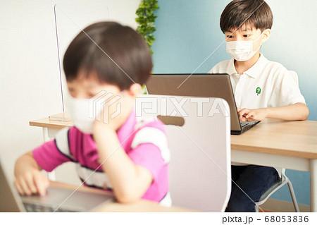 マスクをつけてパソコンを見る男の子 68053836