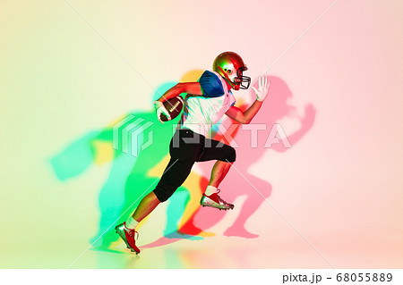 American football player isolated on gradient studio background in neon light with shadows 68055889