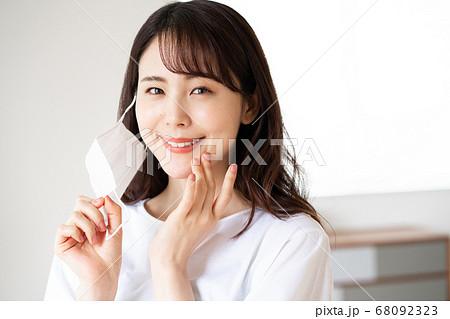 朝マスクをしようとする素顔の若い女性 68092323
