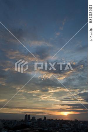 夕日でオレンジ色になった雲とシルエットの街並み 68102681