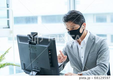 マスクをしてオフィスで仕事をするミドルビジネスマン 68129597