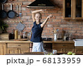 Happy young sick woman dancing in home kitchen 68133959