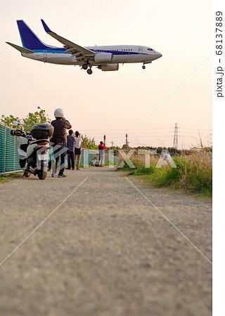 夕暮れの伊丹空港32Lエンド千里川堤防土手・滑走路へ進入する飛行機の通過する風景 68137889