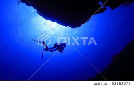 宮古島市にあるダイビングスポットの海底洞窟の女王の部屋の出口を泳ぐダイバーと太陽光 68162672