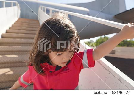 飛行機のタラップを降りる作業着の女の子 68196226