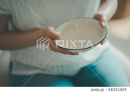 空っぽの皿を持つ女性 68201805