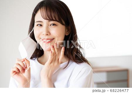 朝マスクをつけようとする若い女性 68226477