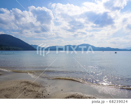 水面が逆光で湖面がきらめく穏やかな田沢湖 68239024