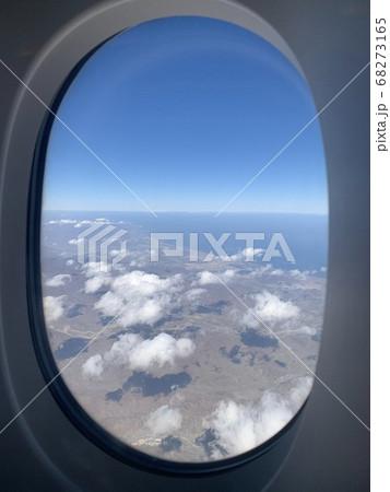旅行中に飛行機の窓から見る雲と景色 68273165