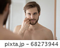 Close up mirror reflection handsome young man touching beard 68273944