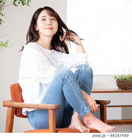 リビングで椅子の上にあぐらをかいて座る若い女性 正方形 68287489