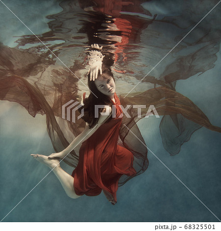 Girl in a red dress with a cloth swims underwater 68325501