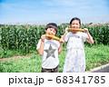 トウモロコシ畑で焼とうもろこしを食べる子供 68341785