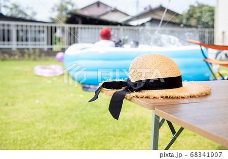 庭でプールをする子供と麦わら帽子 68341907