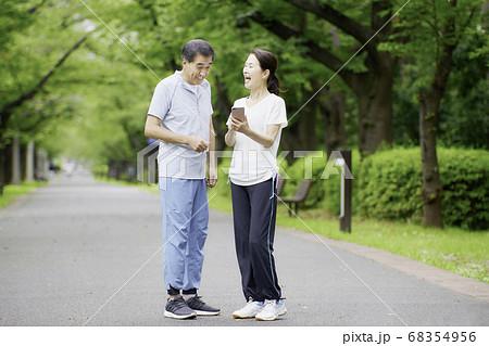 スマホを見て大笑いするシニア夫婦 68354956