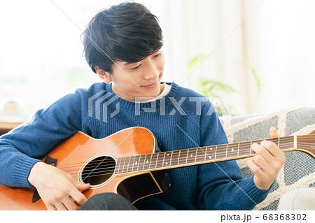 ギターを弾く若い男性 68368302