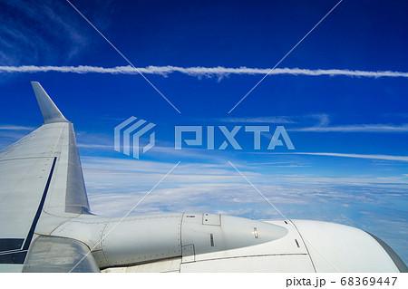 青空に伸びる飛行機雲と飛行機の主翼 68369447