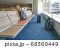 空港のベンチとその周辺に置いてある手荷物 68369449