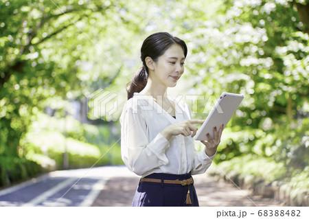屋外でタブレットPCを持っている若いビジネスウーマン  68388482