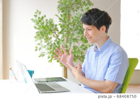 右手を指しながら話すオンライン英会話の講師 68408750