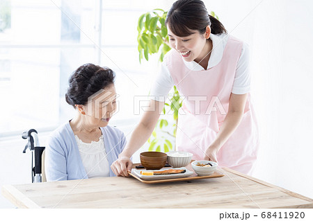 介護イメージ シニア女性に食事を出す介護士 68411920