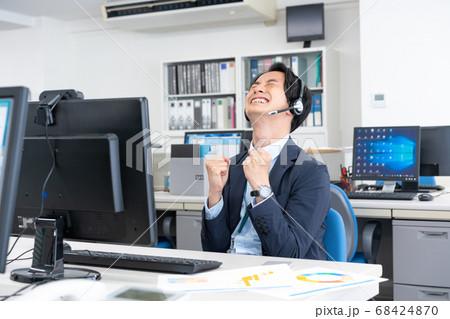 オフィスでウェブ会議 ガッツポーズの若いビジネスマン 68424870