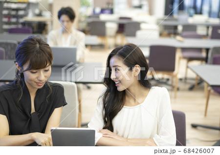 ソーシャルディスタンスを意識しながら、コワーキングスペースで会社の同僚と仕事の打ち合わせをする女性 68426007