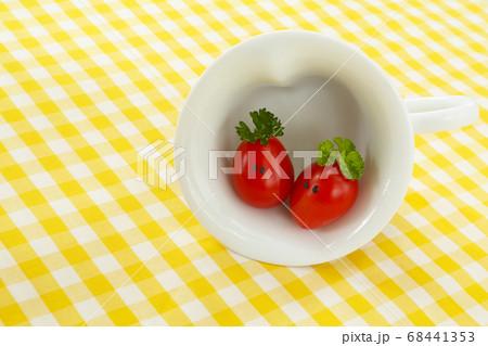 カップの中の顔のある可愛いミニトマトのカップル 68441353