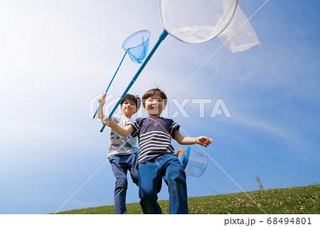 虫とり網を持って走る男の子 68494801
