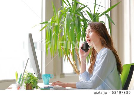 唐突な話に驚く電話中のビジネスウーマン 68497389