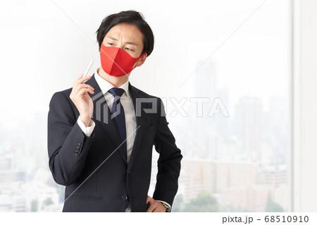 ペンを持つマスク姿のビジネスマン 68510910