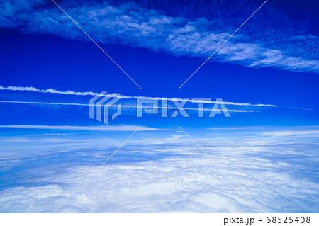 雲上の景色 一直線に伸びる飛行機雲と青空 68525408