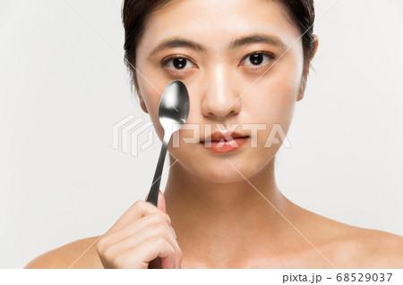 スプーンで目の下をマッサージする女性 68529037