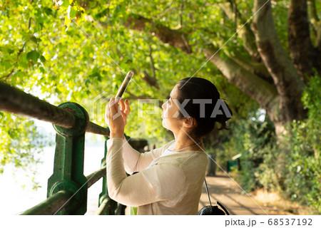 海外旅行の散歩中にスマホで風景写真を撮影する日本人女性 50代 68537192